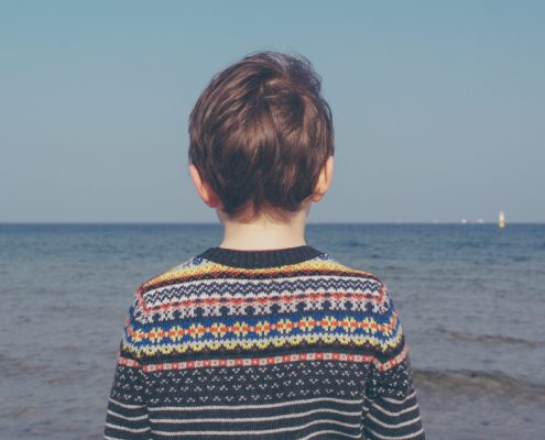 Boy standing on the shore, looking at the sea.