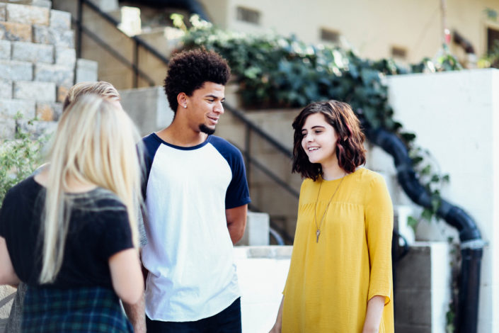 Two girls and a young man talking outside.