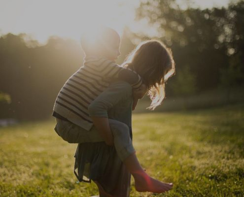 Girl is giving a piggyback ride to a smaller child on a green field, there is a blurred sun behind them,