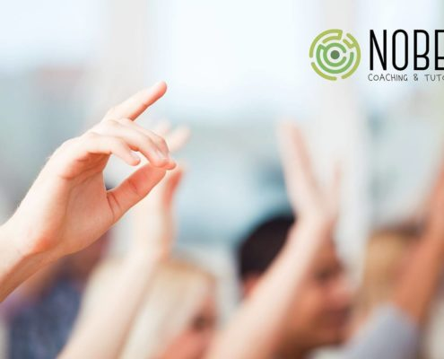 Picture shows several hands raised in the air, all the blurred but one on the left side of the photo. In the right top corner there is a Nobel Coaching and tutoring logo.
