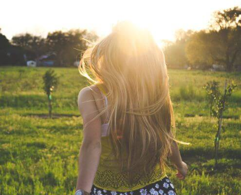 Photo shows the back of the blonde haired girl running into the green field, towards the sun.