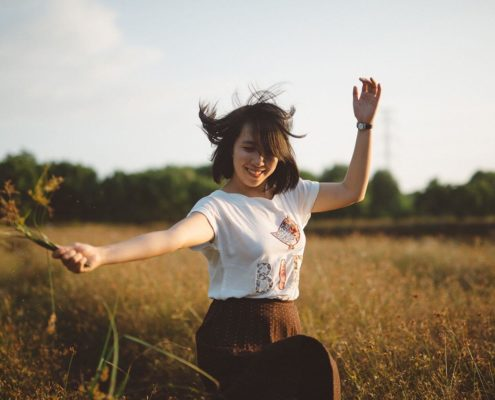 Girl holding flowers and dancing in the field.