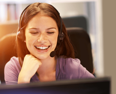 White smiling girl with the long, brown hair looking into the computer screen with her headphone set on.