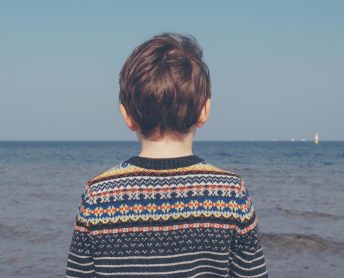 Boy in the colourful sweater is on the middle of the photo, his back turned to the camera, looking at the wide, blue sea,