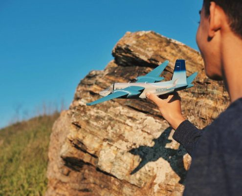Boy on the right side of the photo is seen partly from the back, playing with the blue airplane toy outside. There is a rock, the grass and a clear sky behind him.