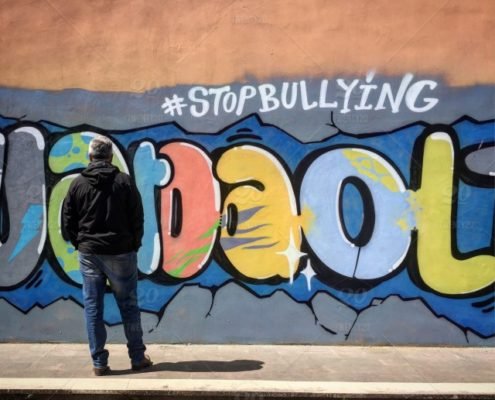 Man in the black jacket stands with his back to the camera against the wall with the graffiti above which there is a hashtag saying 'Stop bullying'