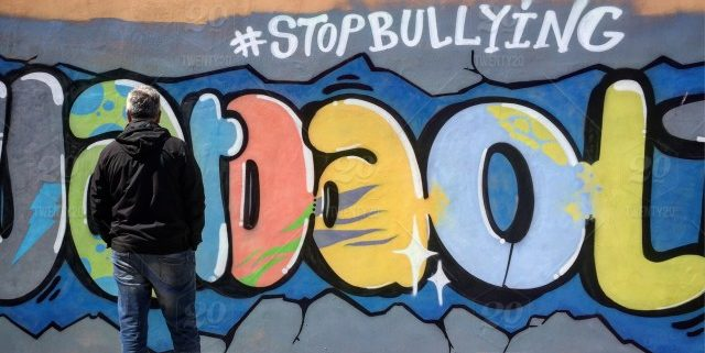 "Man standing in front of grafitti that says ""#stopbullying""."