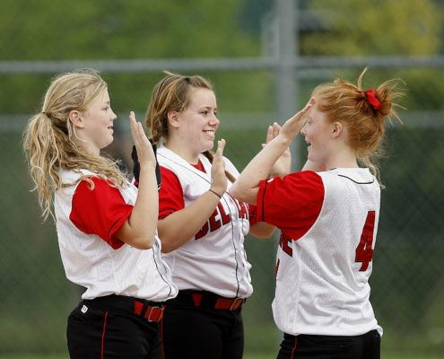 Three girls in softball uniforms celebrating on the field.