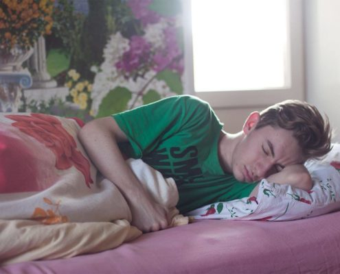 Teenage boy sleeping in a green t-shirt while the light comes through the window behind him,