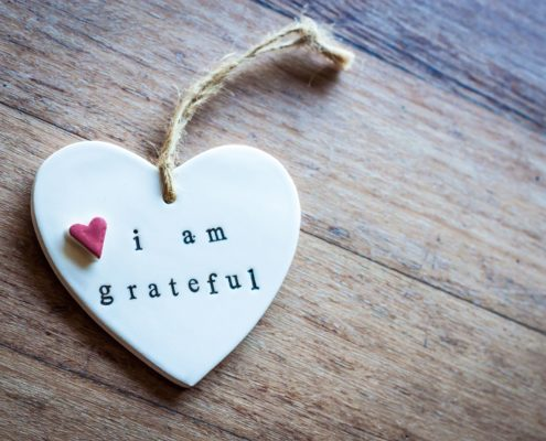 White heart pendant saying 'I am grateful' lies on the left side of the image against the wooden surface