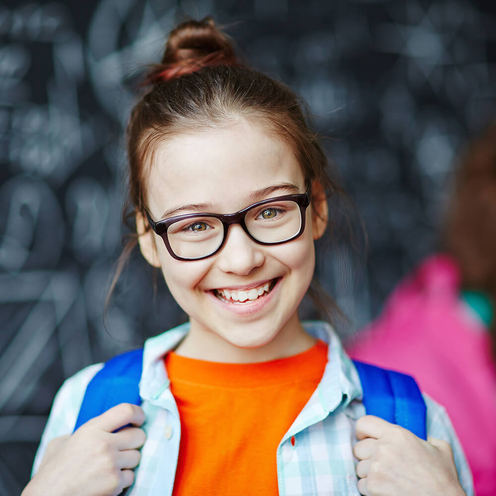A young girl with a backpack on smiling.