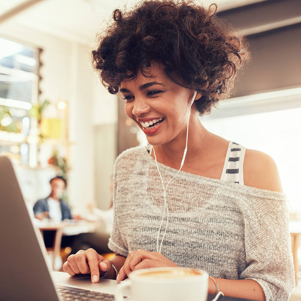 Woman with earphones looking at the laptop and smiling wide.