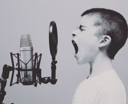 Little boy with very short hair is screaming into the microphone, looking determinate.
