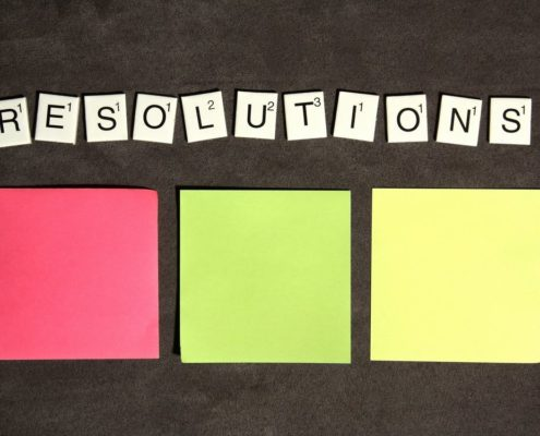 Three notes in red, green and yellow lie against brown surface on the middle of the image, above them there are letters from scrabble saying 'resolutions'