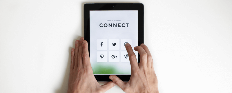 Image shows tablet that says 'Connect' and various social network icons and two hands about to click one of the icons against the white desktop.