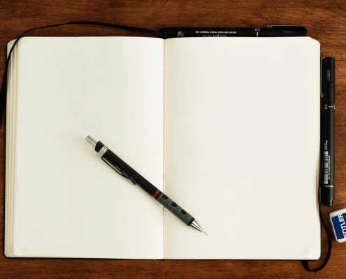 The blank white notebook lies against the brown desk top, and there is a technical graphic pen on top of it lying diagonally.