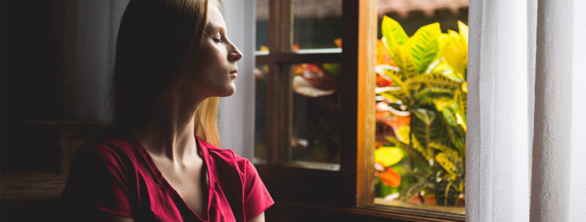 Woman sitting with her eyes closed by a window.