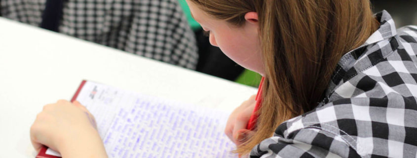 Young woman in plaited shirt with brown hair is writing some long essay on a white piece of paper, she is seen from her side and is sitting on a right side of the image.