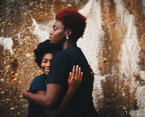 Mother with curly, red hair is hugging her child, they are both wearing black t-shirts, they stand on a left side of the image against brown-white wall.