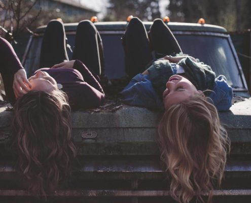Two girls are lying on the top of the old car, the sun is shining and their long hairs are hanging. The girl on the right is smiling,