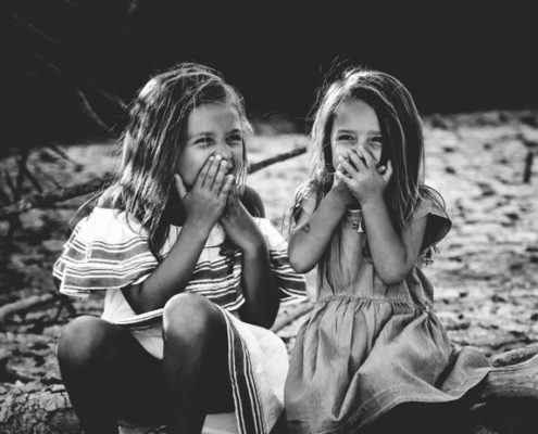 Two young girls laughing together while sitting outside.