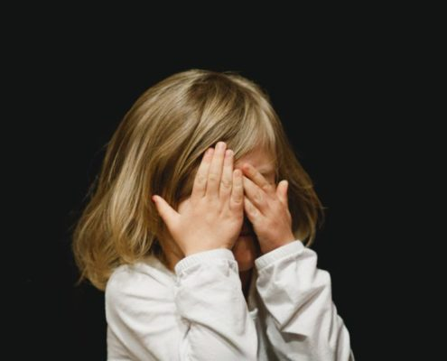 Blonde child is hiding her face in embarrassment, the background is black.