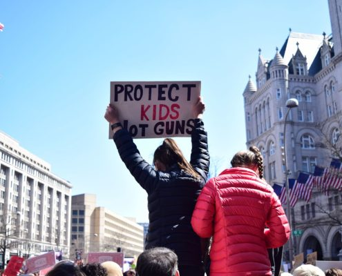 Girl with a ponytail and in a black jacket is standing out of the crowd at the protest, holding a sign saying PROTECT KIDS NOT GUNS. There is a girl with a braid and a red jacket beside her, they both have their backs turned to the camera.