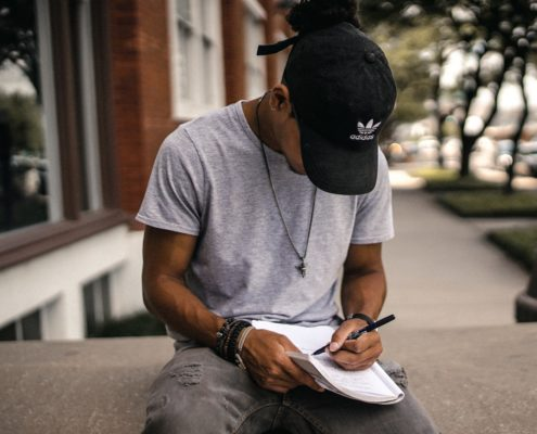 Young man with a hat is sitting down writing piece of white paper.