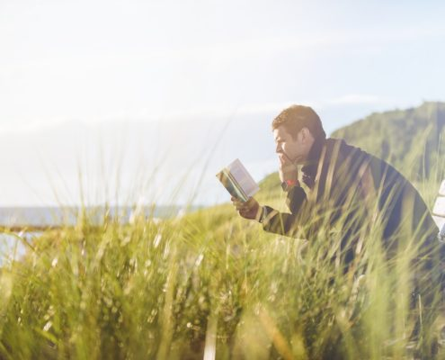Image of a young man looking focused and reading in a field of green grass.