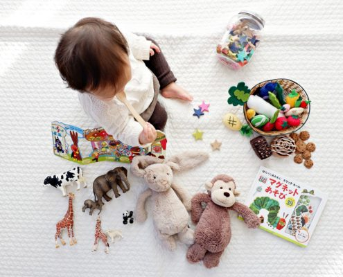 A baby surrounded by toys.