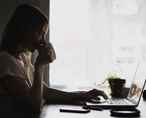 Woman sitting in front of a laptop and drinking coffee.