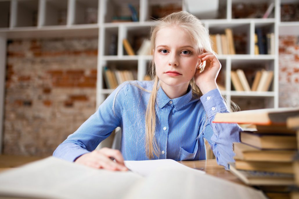 Girl sitting at her desk surrounded by books.