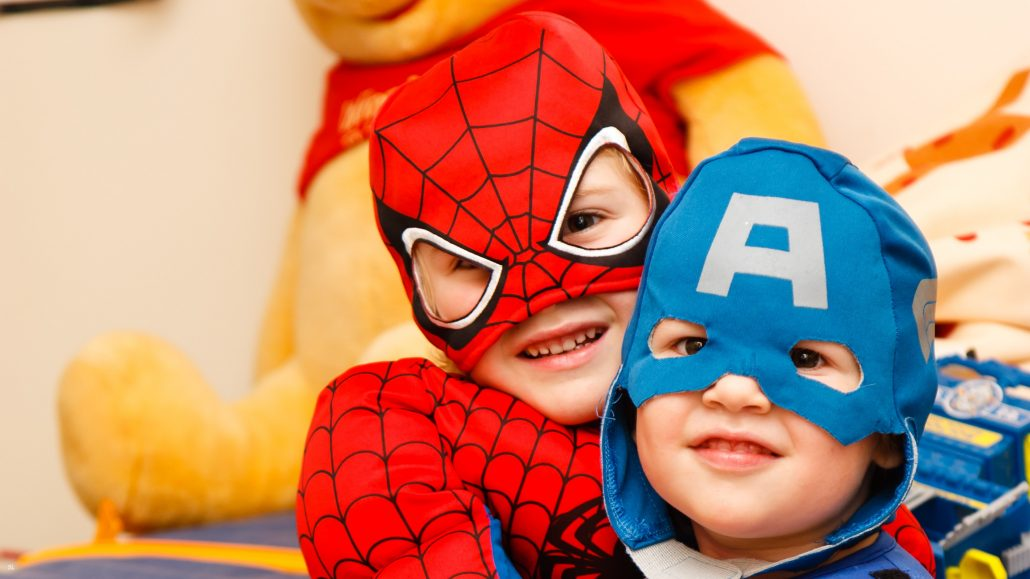 Kids in Spiderman and Captain America costumes smiling.